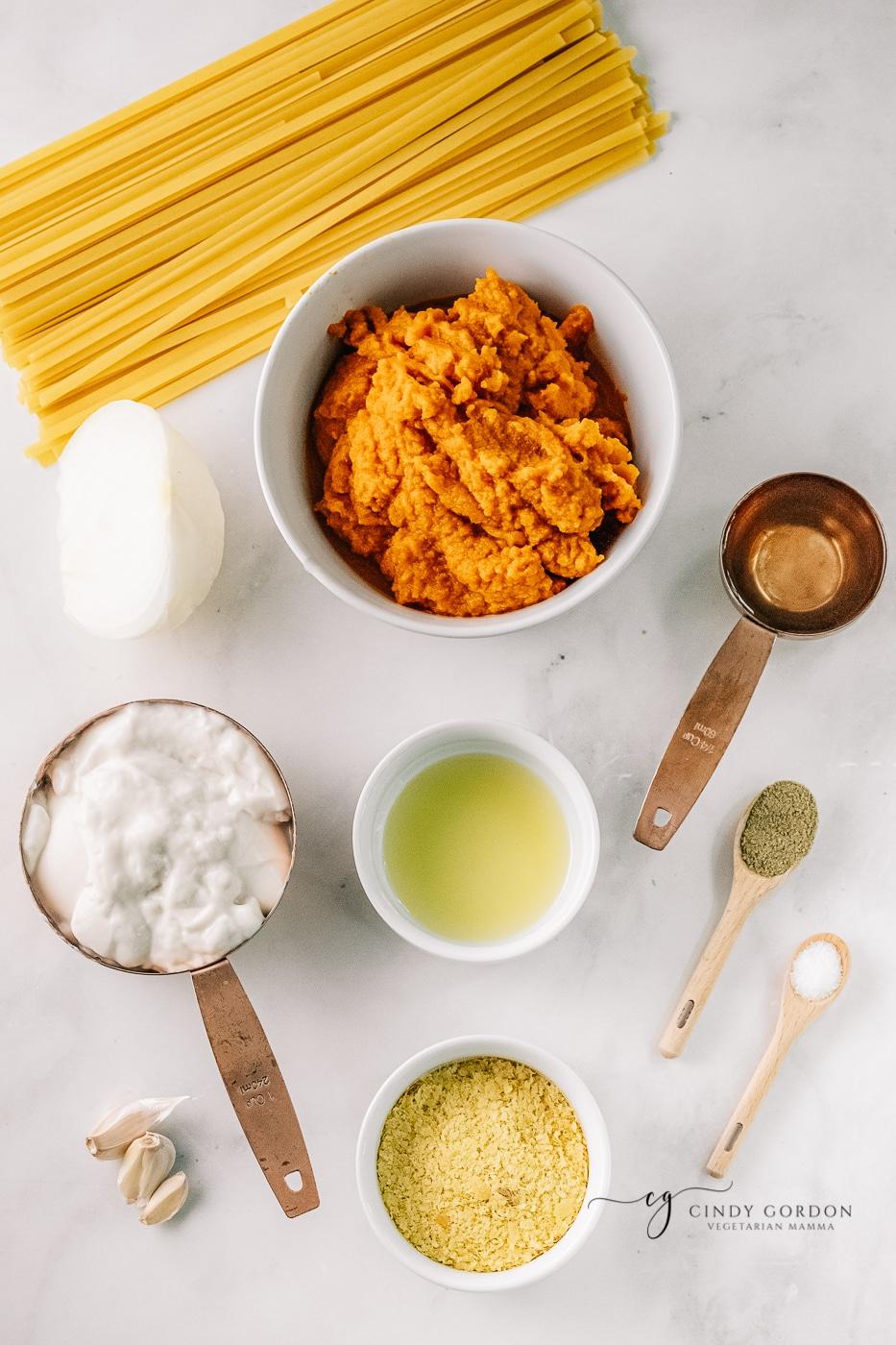 Ingredients for vegan pumpkin alfredo, each in separate bowls on a marble countertop