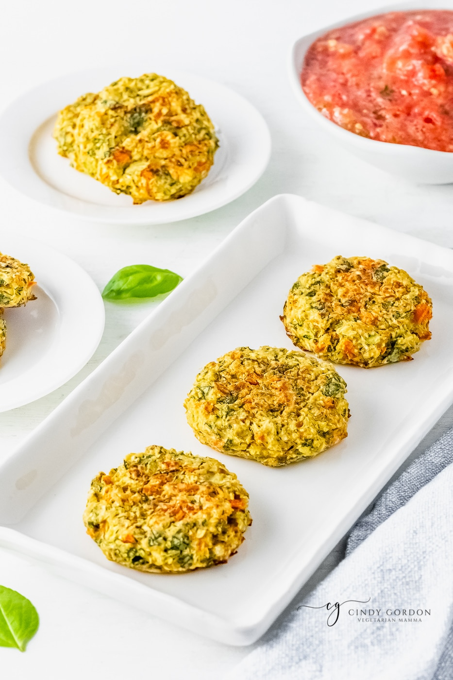 3 zucchini fritters on a white serving platter next to a bowl of salsa