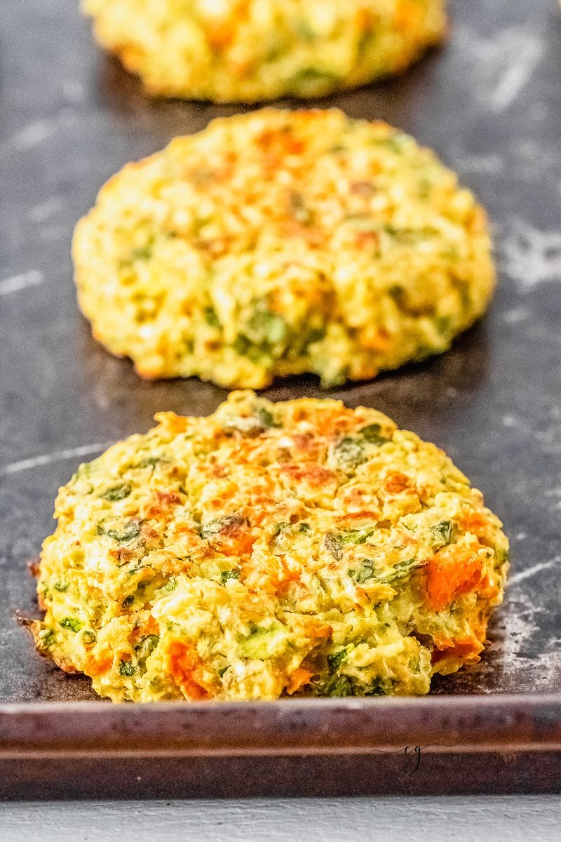 3 baked zucchini fritters on a baking sheet in a line