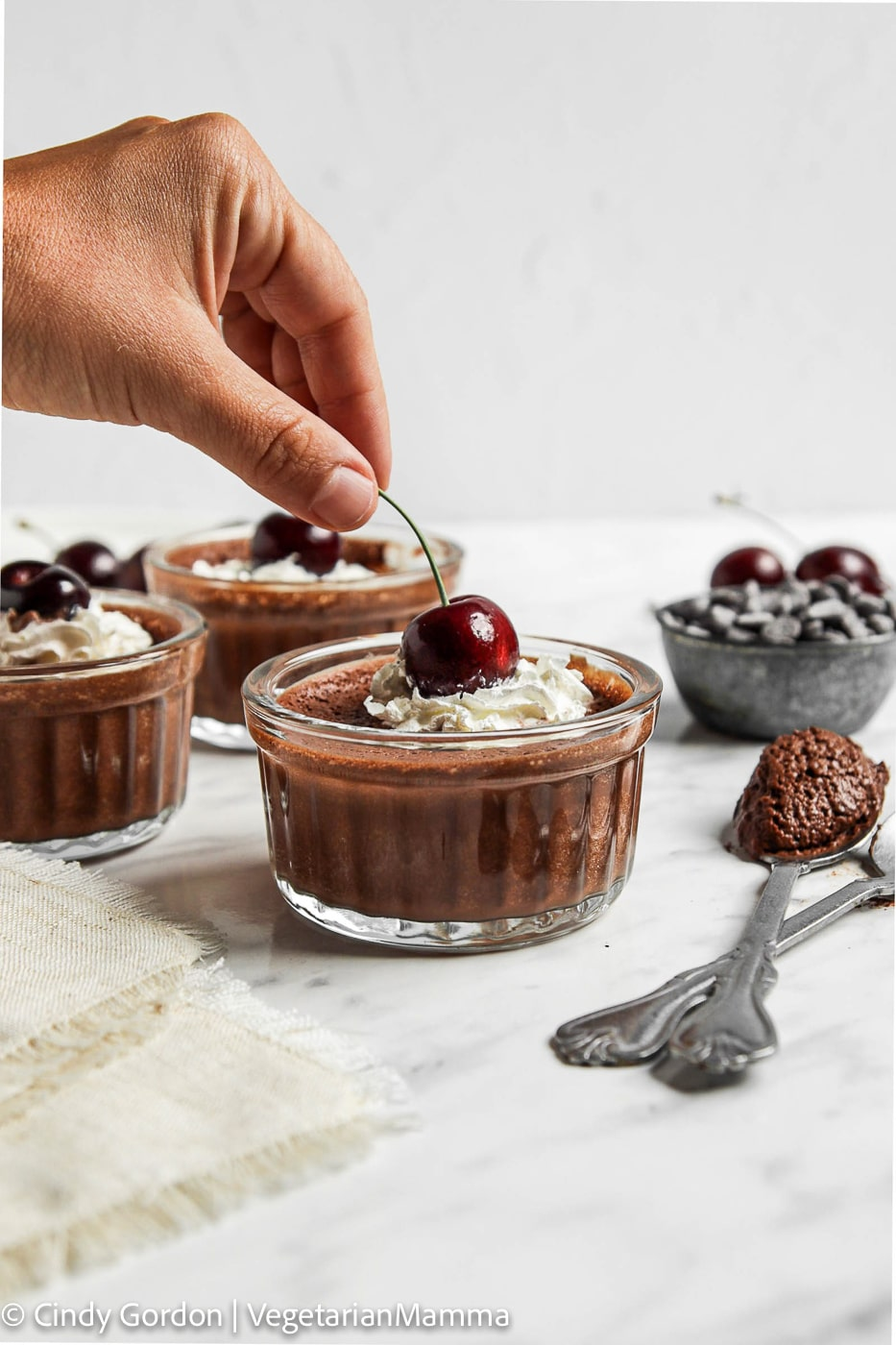 a hand placing a fresh dark cherry on top of a glass dish of vegan chocolate mousse