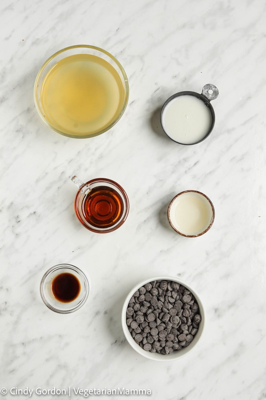 Ingredients for Aquafaba Mousse in separate bowls on a marble countertop