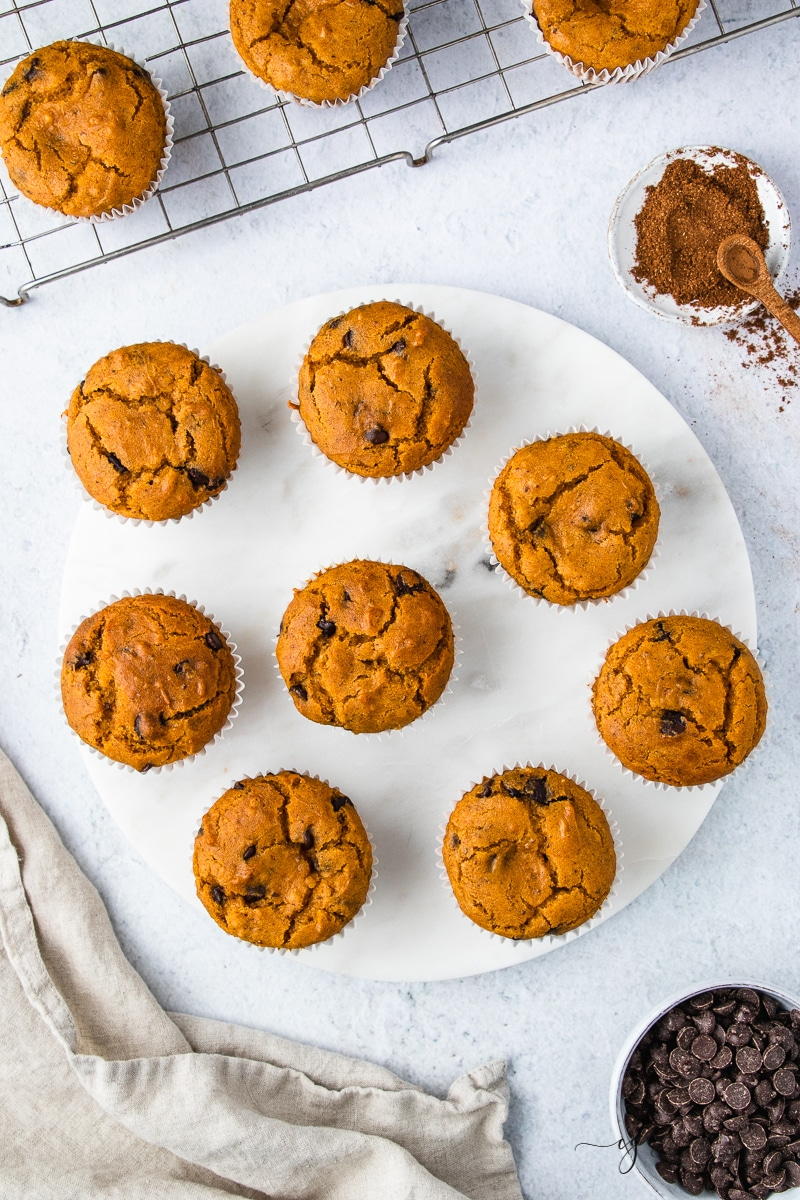 a large white plate with 8 vegan pumpkin chocolate chip muffins on it, shot from above.