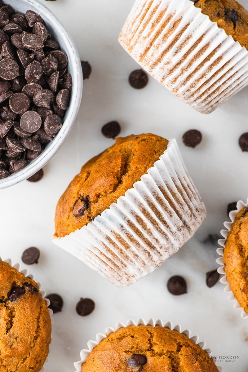 a pumpkin chocolate chip muffin in a white cupcake liner, tipped on it's side, next to a bowl of chocolate chips and more muffins