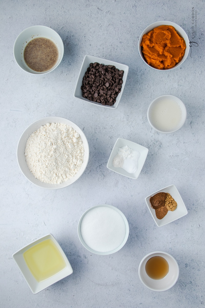 Ingredients in Vegan chocolate chip pumpkin muffins, each in separate bowls on a counter.