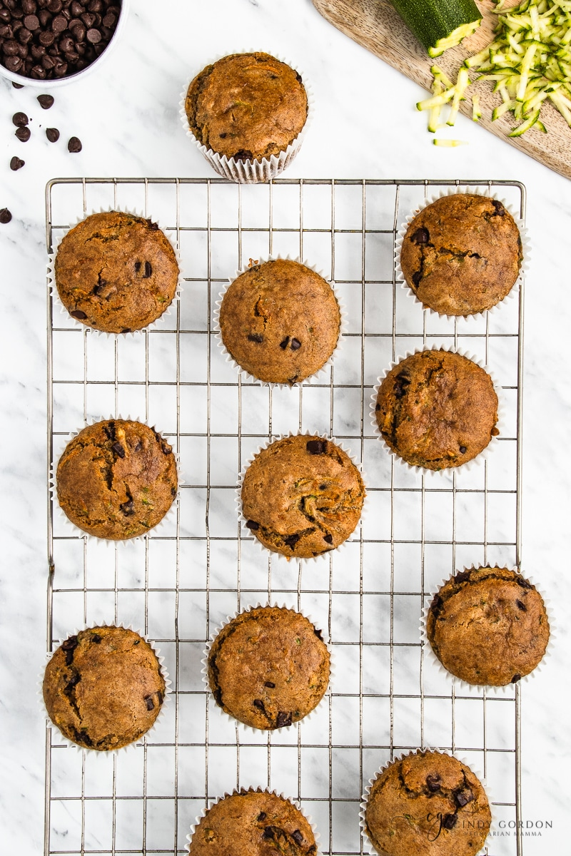 A dozen zucchini muffins on a wire cooling rack surrounded by chocolate chips and grated zucchini