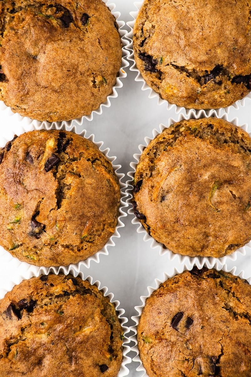 Close-up overhead shot of zucchini chocolate chip muffins in white cupcake liners